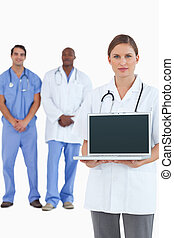 Female doctor showing laptop with colleagues behind her