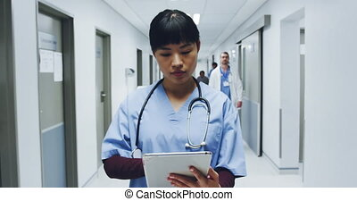 Female doctor standing in hospital corridor using tablet computer 4k