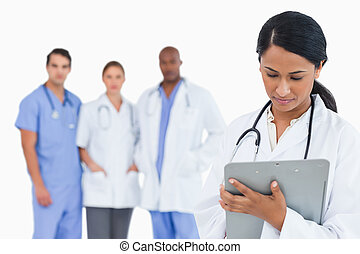Female doctor taking notes on clipboard with staff members behind her against a white background