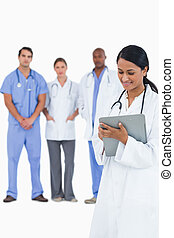 Female doctor taking notes with staff members behind her