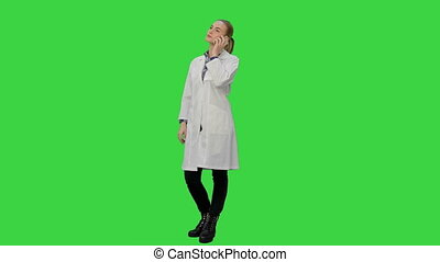 Female doctor talk via cell phone with patient reporting good news on a Green Screen, Chroma Key.