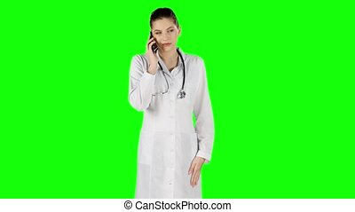 Female doctor talking on mobile phone. Green screen