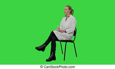 Female doctor talking to a patien and writes in a notebook on a Green Screen, Chroma Key.