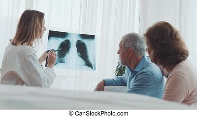 Female doctor talking to a senior couple in office.