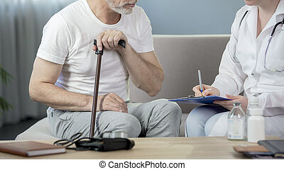Female doctor talking with old patient, writing down medical records, healthcare