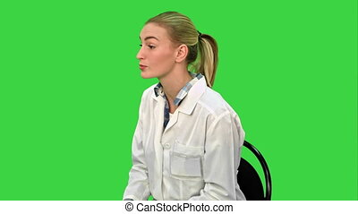 Female doctor talking with patient and writing a recipe on a Green Screen, Chroma Key.