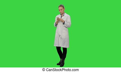 Female doctor text a message using modern smartphone on a Green Screen, Chroma Key.
