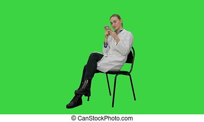 Female doctor uses smartphone to text to a patient on a Green Screen, Chroma Key.