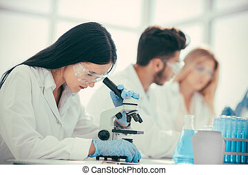 female doctor using a microscope to check for a coronavirus test