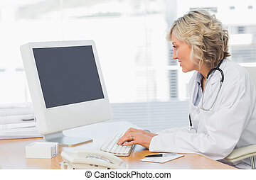 Female doctor using computer in medical office