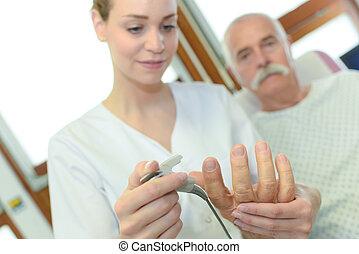 female doctor using lancelet on mans finger in clinic