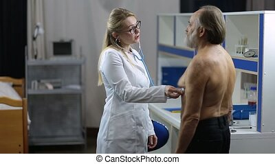 Female doctor using stethoscope to exam patient - Beautiful...