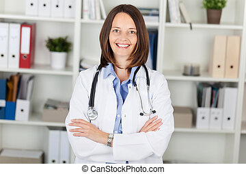 Female Doctor With Arms Crossed Standing Against Shelves