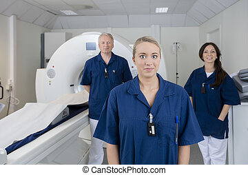 Female Doctor With Colleagues Standing By MRI Machine
