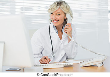 Female doctor with computer using phone at medical office