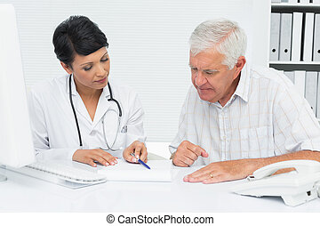 Female doctor with male patient reading reports at medical...