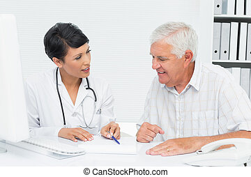Female doctor with male patient reading reports