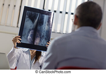 Female doctor working in hospital with patient and x-rays -...