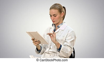 Female doctor working on digital tablet on white background.