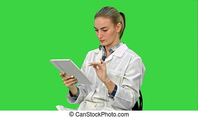 Female doctor working on digital tablet on a Green Screen, Chroma Key.