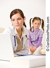 Female doctor write prescription for child