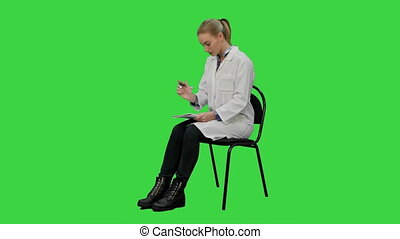 Female doctor writing recipe for a patient on a Green Screen, Chroma Key.