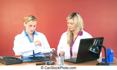 Female doctors signing documents in office