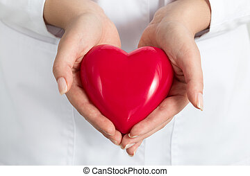 Female doctors's hands holding and covering red heart. Doctor's hands closeup. Medical help, prophylaxis or insurance concept.
