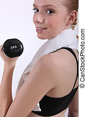 female doing her workout with a dumbbell