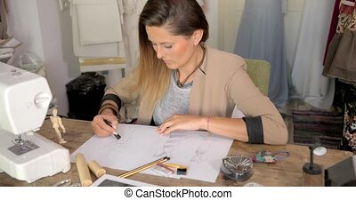 Young stylish woman sitting at table in parlour and drawing sketches of clothing,