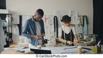 Female dressmaker is measuring fabric with tape-measure while African American man male coworker is using smartphone touching screen. Gadgets and business concept.