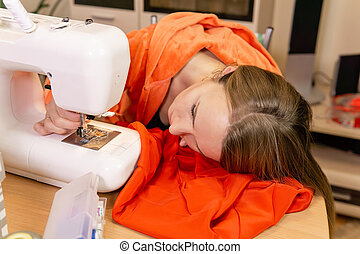 female dressmaker tries to set the needle in a sewing machine
