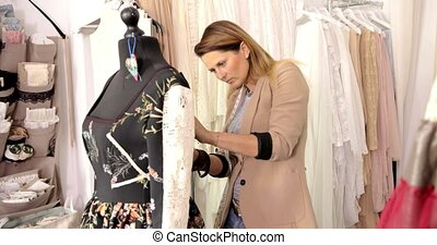 Female dressmaker using mannequin in parlour - Young female...