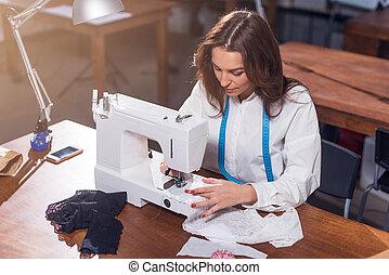 Female dressmaker working with sewing machine, stitching...