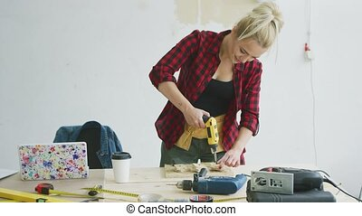 Female drilling wooden plank on workbench - Beautiful...