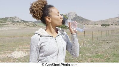 Young pretty female in sportswear drinking water from bottle during workout among beautiful mountains in summer time.