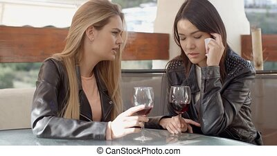 Female drinking with crying friend - Crying young woman with...