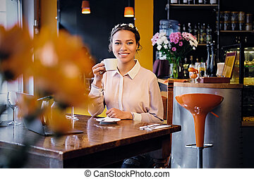 Female drinks coffee in a cafe.