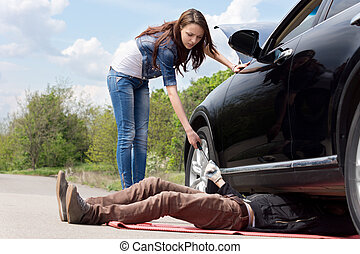 Female driver assisting a mechanic on her car