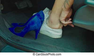 Close-up of hands of african american female driver changing stylish high heels to comfortable shoes, convenient footwear for driving, before road trip.