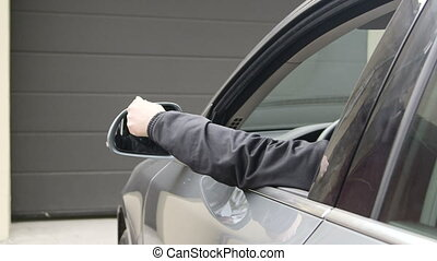 Female driver in car holding remote control to open automatic garage door