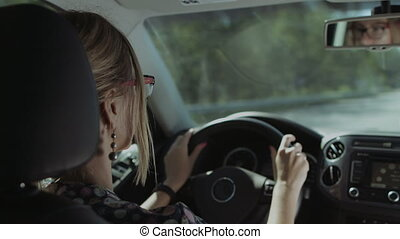 Female driver is reflected in car rear view mirror