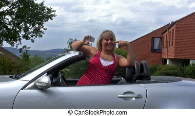 Young woman in her car presenting her driver license