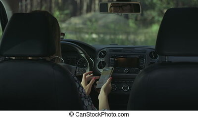Female driver using smart phone in the car