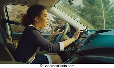 Female driver using smartphone for gps navigation in car