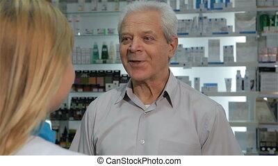 Female druggist gives customer a blister of pills