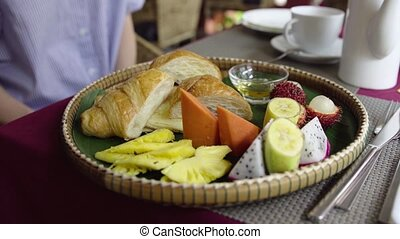 Female eat morning breakfast with tropical fruit, croissant, pancake and honey.