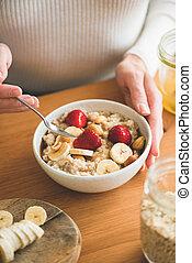 Female eating oatmeal porridge with banana and strawberry for breakfast
