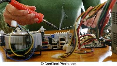 Female electrical engineer soldering a circuit board 4k -...