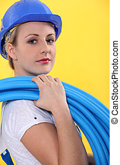 Female electrician carrying coil